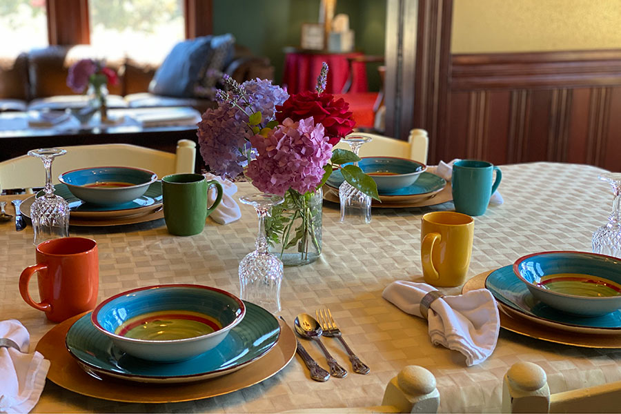 Breakfast in our dining room, breakfast table set with colorful dishes.